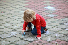 Child drawing with chalk. Preschooler child drawing with chalk on sidewalk royalty free stock photo