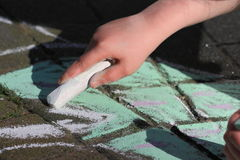 Child drawing with chalk. Child's hand drawing on pavement with chalk Royalty Free Stock Images