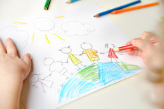 Child drawing children standing on globe. Close up of little blond child drawing group of children standing on globe and holding hands royalty free stock photos