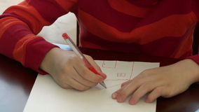 Child drawing a church in a white piece of paper stock video