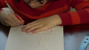 Child drawing a church in a white piece of paper stock video footage