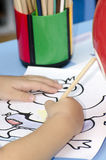 Child drawing. Child colouring in a drawing with colourful pencils royalty free stock photography