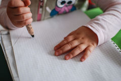 Child drawing with crayons. On a piece of paper stock photo