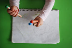 Child drawing with crayons. On a piece of paper royalty free stock image
