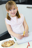 Child drawing with crayons, sitting at table in kitchen Stock Photo