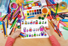 Child drawing cute happy cartoon people in row, top view hands with pencil painting picture on paper, artwork workplace