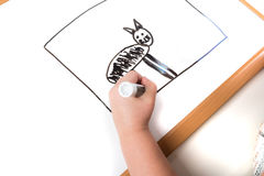 Child drawing on a dry erase board Stock Images