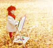 Child drawing on easel Autumn Park. Creative kid Royalty Free Stock Images
