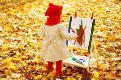 Child drawing on easel in Autumn Park. Creative kids development concept royalty free stock photo