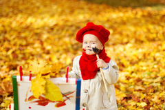 Child drawing on easel in Autumn Park. Creative kids development. Child drawing on easel in Autumn yellow park. Creative kids development concept stock photos