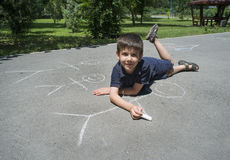 Child drawing family on asphalt. In a park stock photography