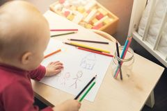Child drawing family picture with colored pencils. At home stock photos