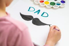 Child is drawing Father`s day greeting card