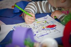 Child is drawing with green pen Stock Photo