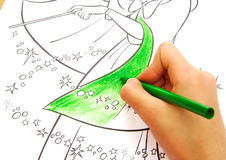 Child drawing with a green wax crayon. Royalty Free Stock Photos