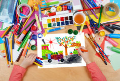 Child drawing harvesting crop in village, top view hands with pencil painting picture on paper, artwork workplace Stock Photography