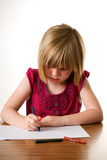 Child drawing with her crayon Stock Photos