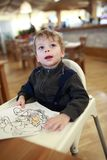 Child drawing at highchair. In a cafe stock photography