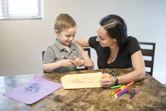 Child drawing with his mom, sitting at table in kitchen at home Stock Photos