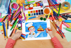 Child drawing holiday cake and cook, top view hands with pencil painting picture on paper, artwork workplace