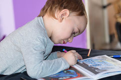Child drawing at home. Cute blond Child playing at home, drawing coloring book stock photo