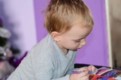 Child drawing at home. Cute blond Child playing at home, drawing coloring book stock images