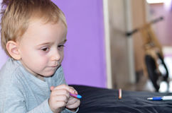 Child drawing at home. Cute blond Child playing at home, drawing coloring book royalty free stock photo