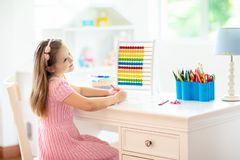 Child drawing. Kids paint. Girl after school. Child drawing rainbow. Kid painting at home. Little girl doing homework after school. Kids desk with abacus in stock photos