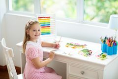 Child drawing. Kids paint. Girl after school. Child drawing rainbow. Kid painting at home. Little girl doing homework after school. Kids desk with abacus in stock images