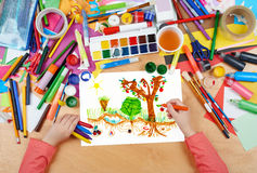 Child drawing kitchen garden with vegetables , top view hands with pencil painting picture on paper, artwork workplace Royalty Free Stock Photos