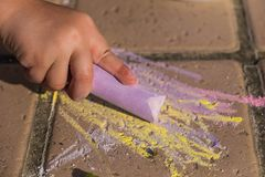 Child drawing with large color chalk on the floor outdoors. Children creativity conceptual background royalty free stock photography