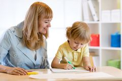 Child drawing with mother Stock Photography