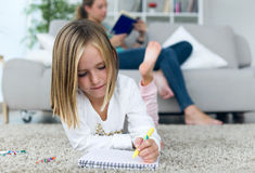 Child drawing on the notebook while your mother reading a book a Stock Images