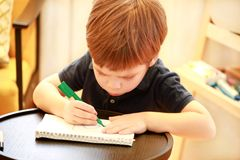 Child is drawing and painting with felt pen on paper of spiral notebook on small wooden table in living room at home. Childhood. royalty free stock photo