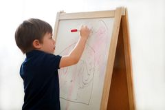 Child is drawing and painting with felt pen on paper of wooden drawing board artist easel for kids and children at home. Childhood. Cute little boy, kid draws stock photography