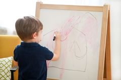 Child is drawing and painting with felt pen on paper of wooden drawing board artist easel for kids and children at home. Childhood. Cute little boy, kid draws stock image