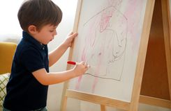 Child is drawing and painting with felt pen on paper of wooden drawing board artist easel for kids and children at home. Childhood. Cute little boy, kid draws stock photo