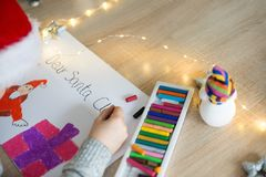 Child drawing a pastel drawing of Santa Claus. And present royalty free stock photos