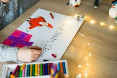 Child drawing a pastel drawing of Santa Claus. And present stock image