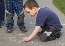Child drawing on the pavement with chalk Royalty Free Stock Photos