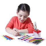 Child drawing with pensil using a lot of painting tools Royalty Free Stock Images