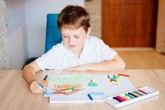 Child drawing picture of boy going to school. Back to school royalty free stock photo