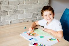 Child drawing picture of boy going to school. royalty free stock images