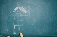 Child drawing picture on chalkboard stock photo
