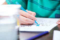 Child drawing picture. Close-up partial view of child drawing picture in coloring book stock photos