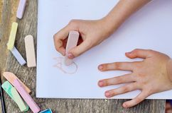 Child is drawing a picture on white paper with a colorful chalk. Closeup view of hands and drawing royalty free stock images