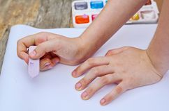 Child is drawing a picture on white paper with a colorful chalk. Closeup view of hands and drawing stock images