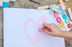 Child is drawing a picture on white paper with a colorful chalk. Closeup view of hands and drawing royalty free stock photo