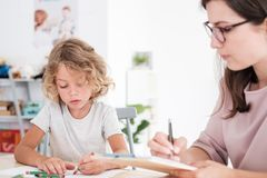 Child drawing pictures during meeting with therapist for orphans. Concept stock image