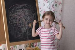 Child is drawing with pieces of color chalk on the chalk board. Girl is expressing creativity and looking at the camera. Child is drawing with pieces of color royalty free stock images